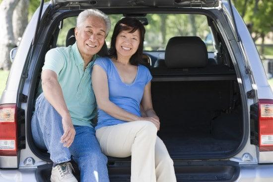 Couple sitting in back of vehicle